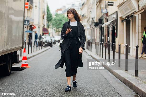 A model holds and iPhone and exits the Hermes Resort SS17 presentation in a black collarless trench coat black dress and black Nike sneakers n a...