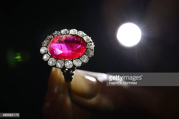 A model holds the Queen MariaJose ruby ring during a press preview by auction house Sotheby's in Geneva on November 4 2015 The ring set with an oval...