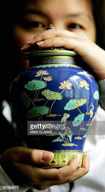 Model holds up one of a pair of Famille Rose fahua style jars and covers with Qianlong impressed six character sealmarks from the period prior to an...