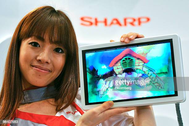 A model holds up Sharp Corp's 106 inch 3D ebook tablet computer prototype at a media preview in Tokyo Japan on Monday April 12 2010 Sharp Corp said...