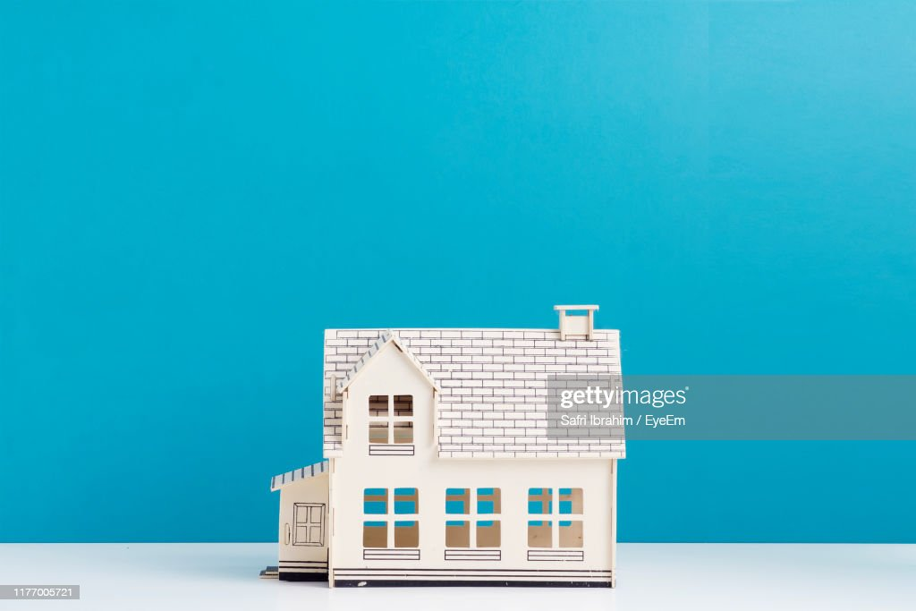 Model Home On Table Against Blue Wall : Stock Photo