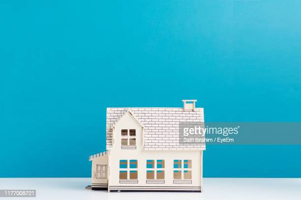 model home on table against blue wall - model home stock pictures, royalty-free photos & images