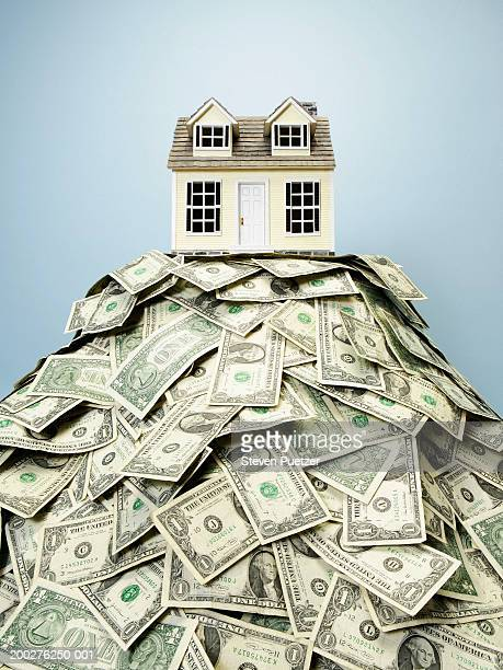 Model home resting on top of US paper currency
