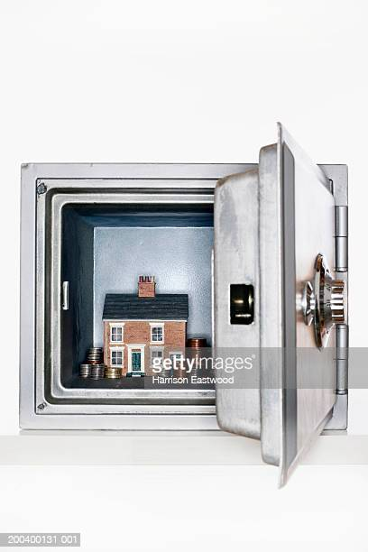 Model house and stacked coins in safe, view through open door