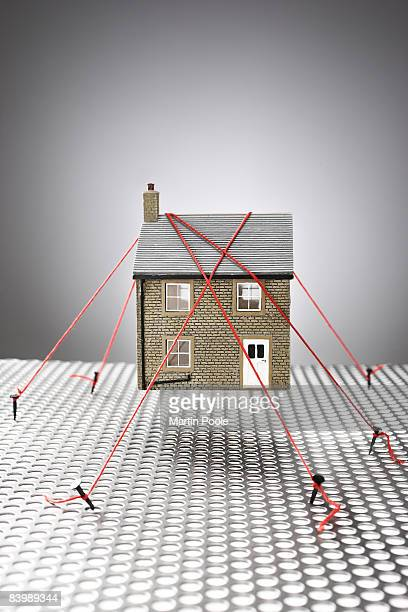 model house being held down by rope