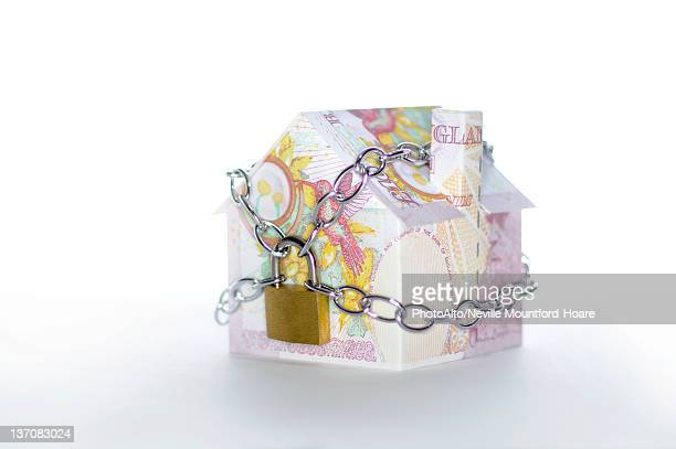 Model house folded with British pound banknotes chained and padlocked