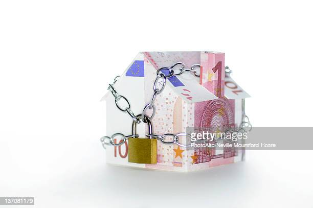 Model house folded with euro banknotes chained and padlocked
