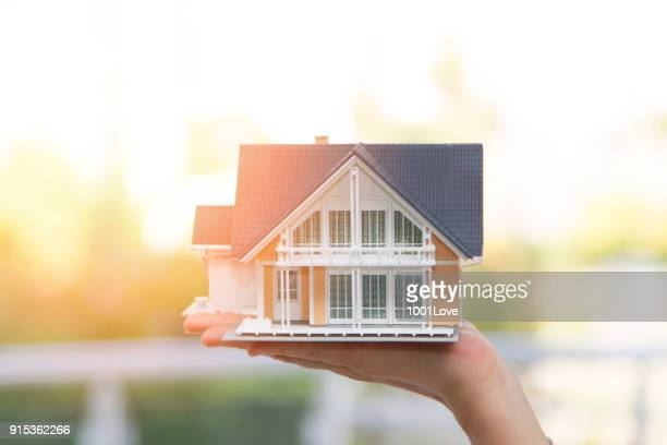 model house in woman hand - home insurance stock pictures, royalty-free photos & images