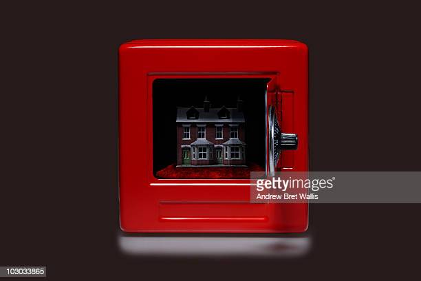 model house inside an open red safe