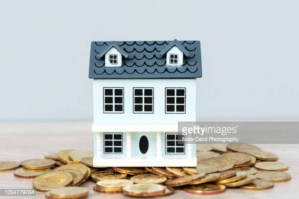model house on top of gold coins - dollhouse stock pictures, royalty-free photos & images