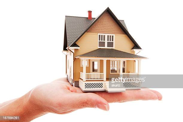 Model house sitting on top of female hand isolated