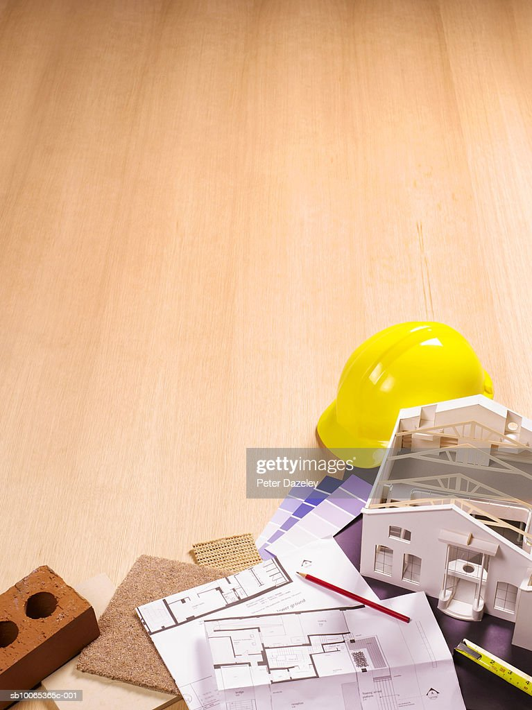 Model house with blueprints and hard hat, elevated view : Foto stock