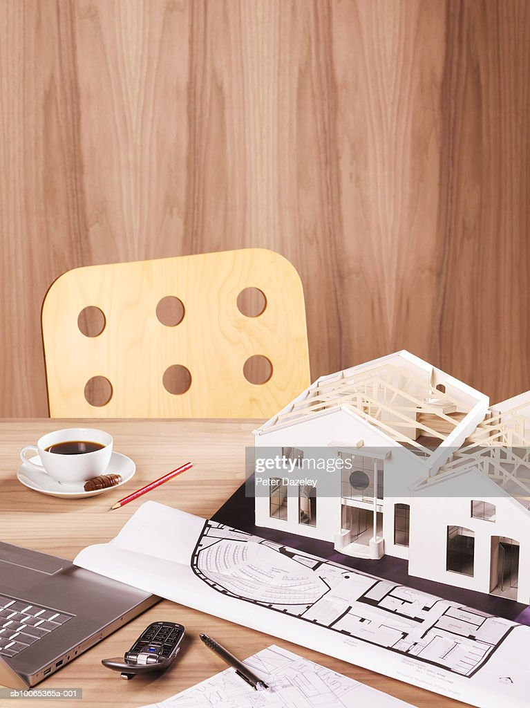 Model house with blueprints and laptop on table : Foto stock