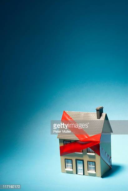 model house with red tape around it - bureaucracy stock pictures, royalty-free photos & images