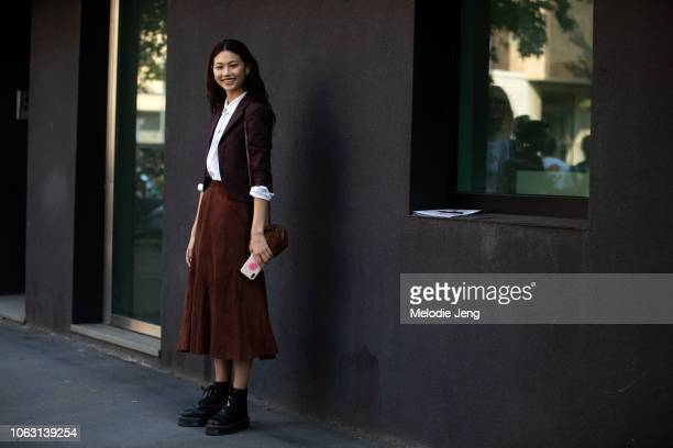 Model Hoyeon Jung wears a brown blazer white top brown suede skirt small brown Adidas purse and black combat boots during Milan Fashion Week...
