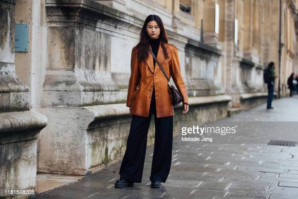 Model Hoyeon Jung wears a brown leather blazer Louis Vuitton bag black pants and black boots after the Beautiful People show during Paris Fashion...