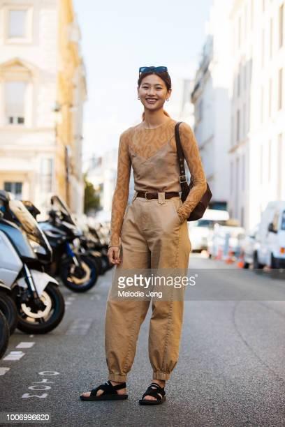 Model Hoyeon Jung wears Max Mara sunglasses a tan Acne Studios top brown Coach bag tan I Am Gia pants and black New Balance sandals after Fendi...