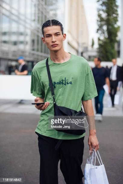 Model Huang Shixin wears a green t-shirt, blak cross-body bag after the Dior Men show during Paris Fashion Week Men's Spring/Summer 2020 on June 21,...