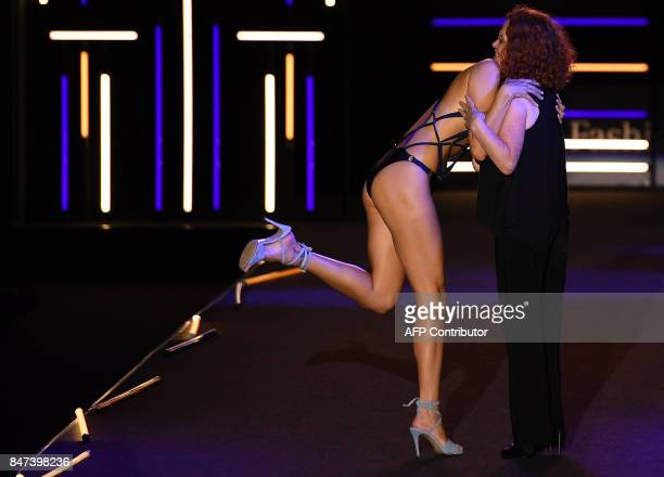 A model hugs Spanish designer Dolores Cortes on the catwalk after presenting her Spring/Summer 2018 collection during the Madrid Fashion Week in...