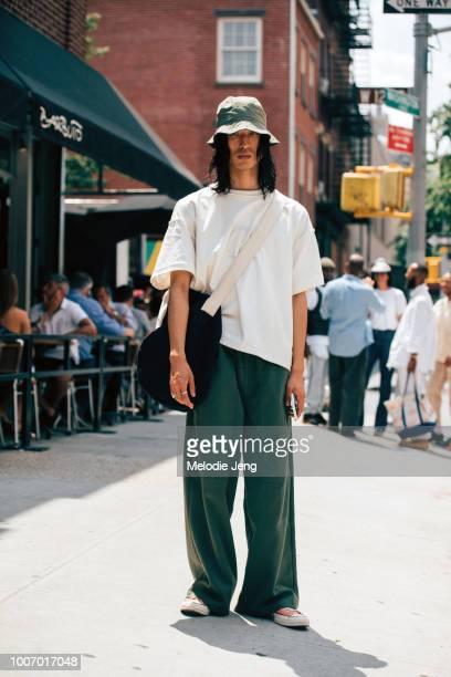 b5ed044a6e9 Model Hunter Chung wears a green bucket hat oversized white shirt crossbody  duffle bag and loose