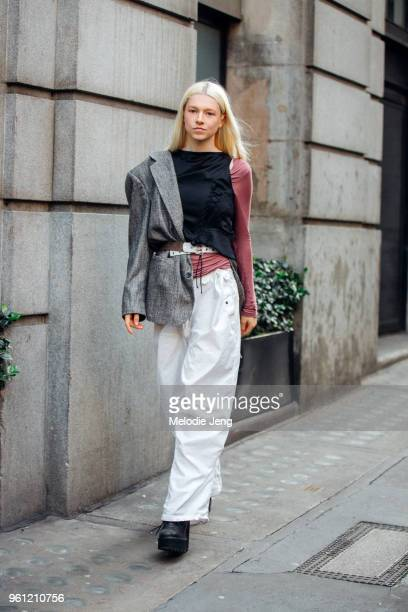 Model Hunter Schafer wears an asymmetrical outfit with a blazer only on one shoulder and loose white pants during London Fashion Week Spring/Summer...
