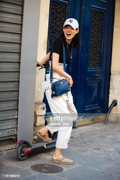 Model Hyun Ji Shin wears a white New York Yankees cap, Paco Rabanne top, blue Prada bag, white overalls, and brown sandals and poses with a Bird...