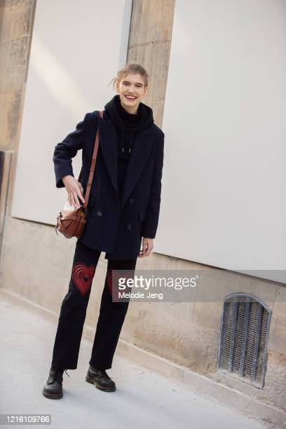 Model Ilya Vermeulen wears a blue blazer, small brown Gate Loewe bag, pants with hearts, and black shoes after the Margiela show on January 22, 2020...