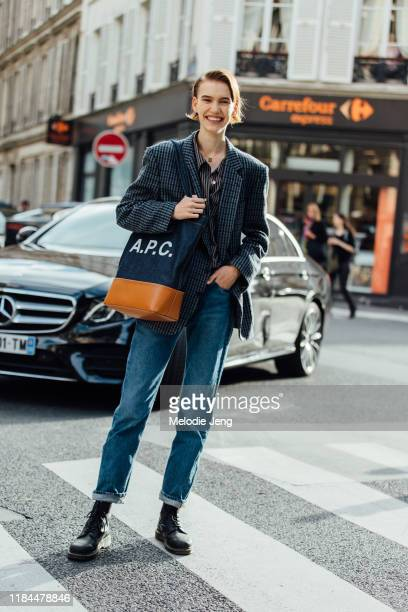 Model Ilya Vermeulen wears a checked blazer, A.P.C. Denim and leather tote bag, blue jeans, and black boots after the APC show during Paris Fashion...