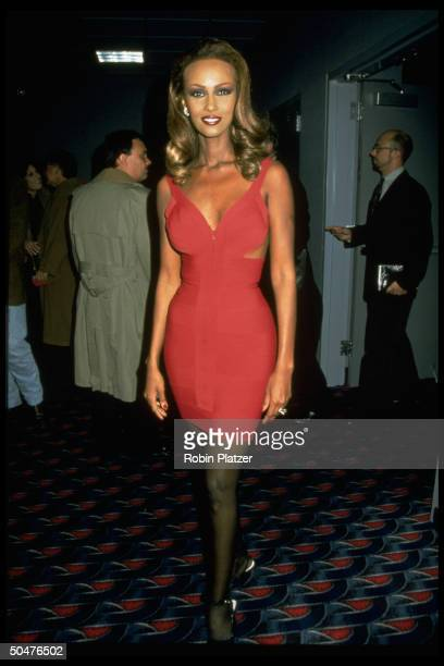 Model Iman wearing hot pink Herve Leger skin tight minidress w plunging neckline