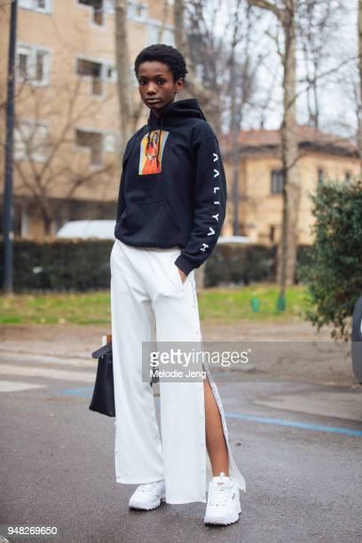 Model Imari Karanja wears a black Aaliyah hoodie white Tory Burch button pants and white chunky disruptor Fila sneakers during Milan Fashion Week...