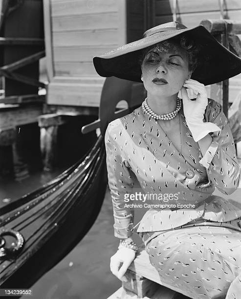 A model in a Christian Dior outfit sitting by a gondola Venice 3rd June 1951