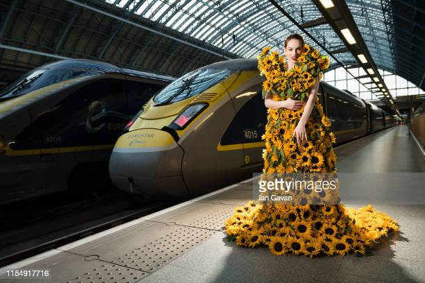 A model in a dress made of sunflowers poses next to a Eurostar train on the platform at St Pancras International as Eurostar introduces third service...