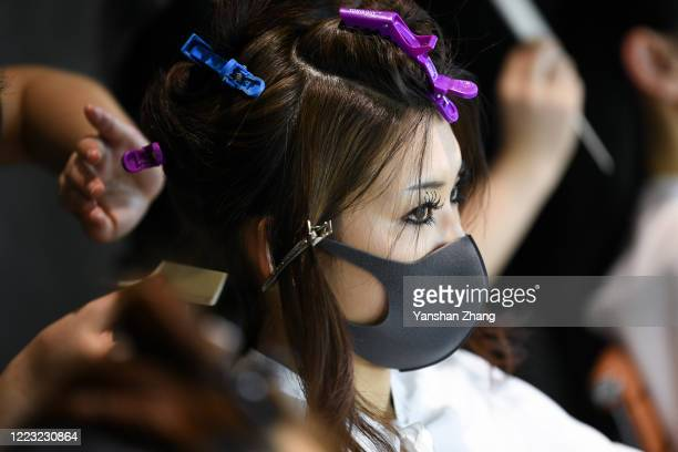 Model in a face mask prepares backstage before the YONG X collection show by Chinese designer Yong Xing during the China Fashion Week 2020/2021 A/W...