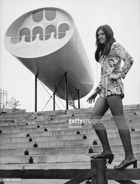 Model in a minidress standing on a fence with a one-bedroom apartment built in tube-form elevated on pillars in the background, in the grounds of the...