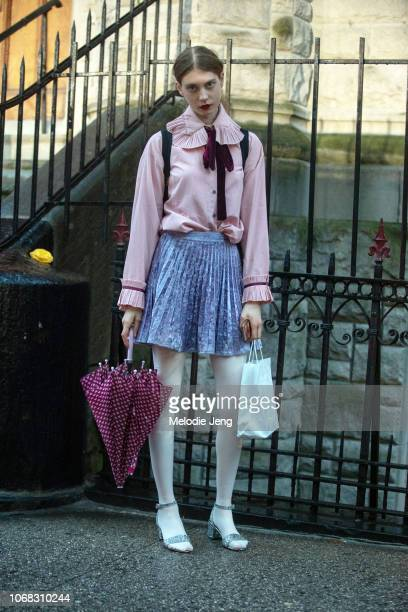 A model in a pink blouse purple skirt pink umbrella white tights and silver sparkly heels after the Rodarte show during New York Fashion Week...