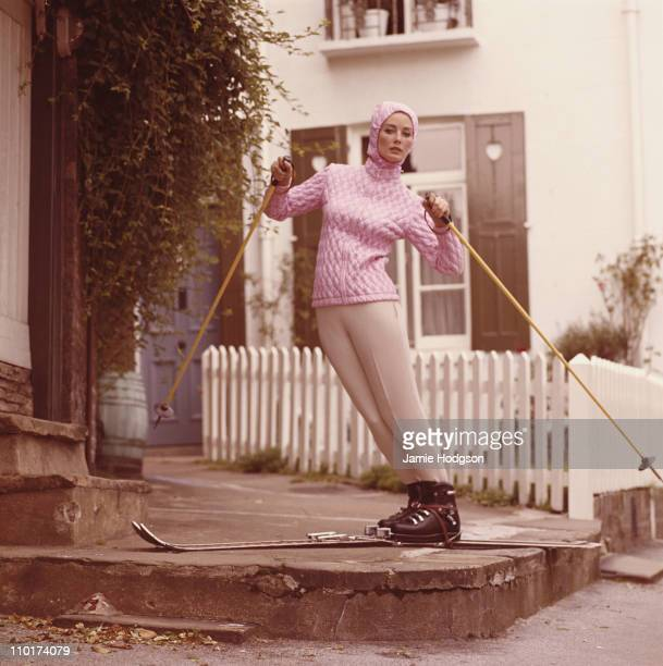 A model in a pink quilted jacket feigns skiing on a village street corner circa 1965