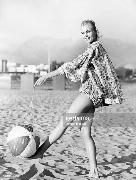 Model in a wide linen tunic playing with a ball on the beach ca1957 Photographer Regine Relang Published by 'Brigitte' 10/1957Vintage property of...
