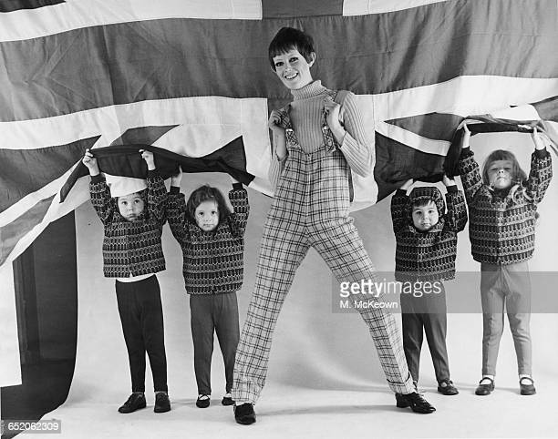 A model in Ginger Group dungarees by Mary Quant an Acrilan sweater and Lotus brogues poses with a group of children in quilted anoraks and stretch...