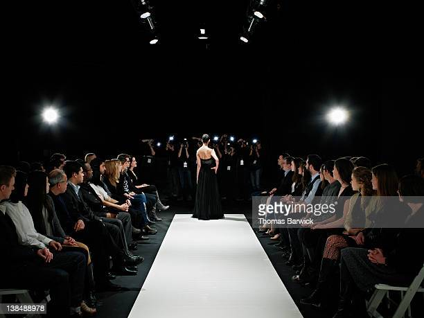 model in gown at end of catwalk posing - catwalk stock pictures, royalty-free photos & images