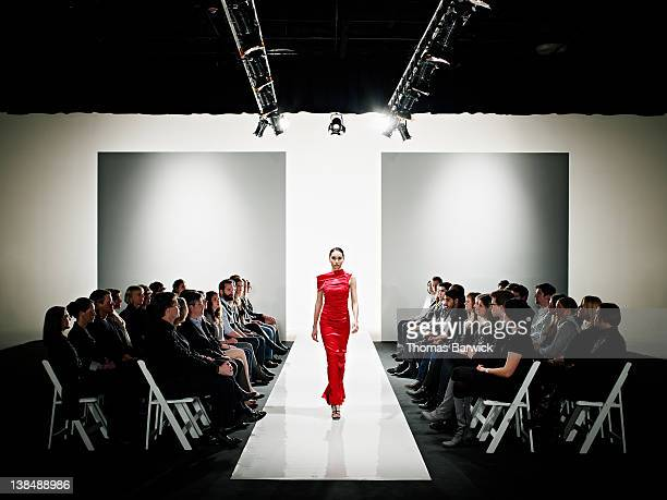model in gown walking down catwalk at fashion show - fashion show stock pictures, royalty-free photos & images