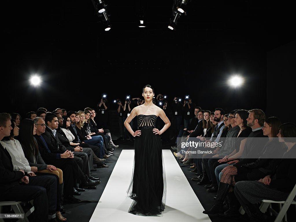 Model in gown walking down catwalk : Stock Photo