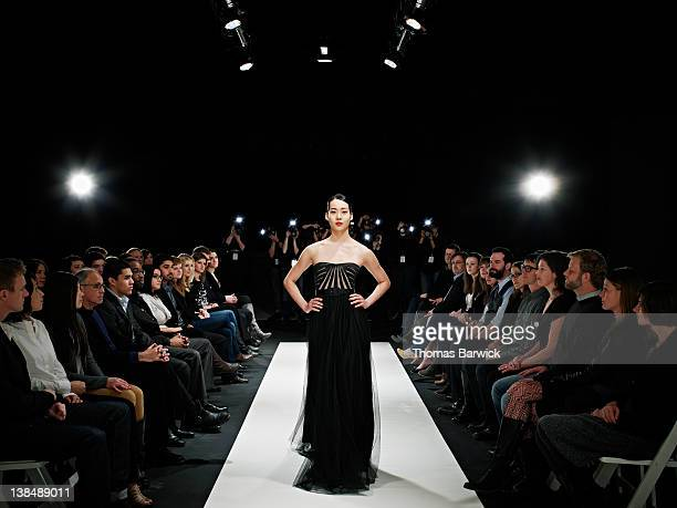 model in gown walking down catwalk - fashion show stock pictures, royalty-free photos & images