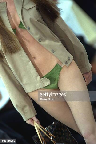 Model in pine green twopiece swimming costume and almond green jacket