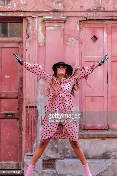 model in pink polka dot dress and gloves with black hat in london jumping of happiness - fashion stock pictures, royalty-free photos & images