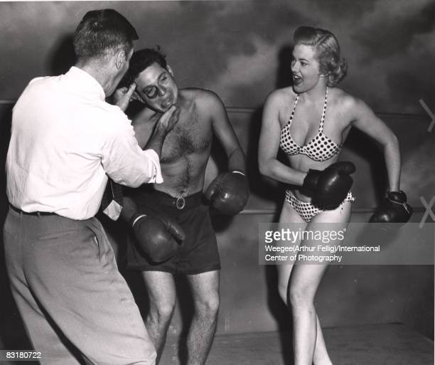 A model in polka dotted bikini and high heels in boxing ring knocking out male boxer with black eye New York ca1950s Photo by Weegee/International...