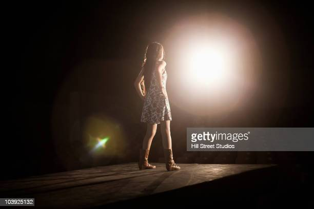 model in spotlight on fashion runway - catwalk stock pictures, royalty-free photos & images