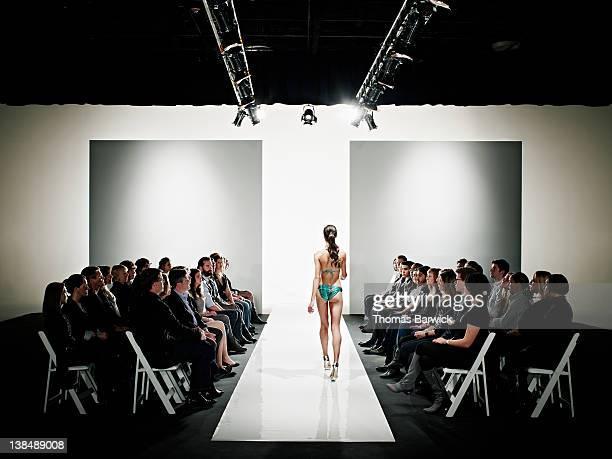 Model in swimsuit walking down catwalk