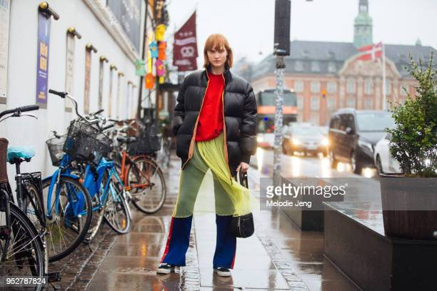 Model Ina Maribo Jensen wears a black down jacket, red top, and sheer yellow dress over blue jogger pants at Copenhagen Fashion Week Autumn/Winter 18...