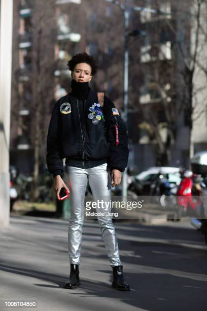 Model Indi Irvin wears an Alpha Industries NAS MA-1 Flight Jacket with pins, silver pants, black boots after the Wood Wood show during Milan Men's...