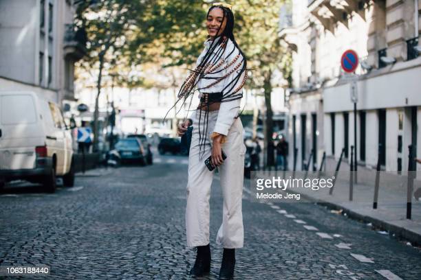 Model Indira Scott shows off the braids in her hair and wears yellow sunglasses a white denim cropped jacket khaki pants blue purse and black boots...